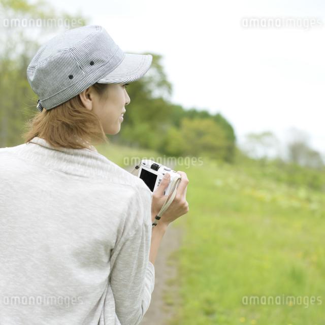 ミラーレス一眼カメラを持つ女性の後姿の写真素材 [FYI04553324]
