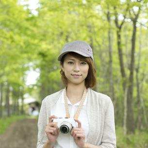 ミラーレス一眼カメラを持ち微笑む女性の写真素材 [FYI04553325]