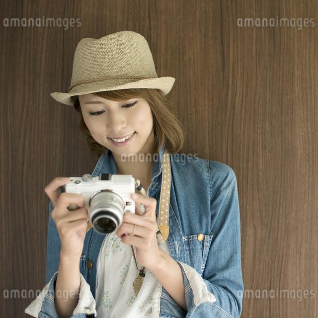 ミラーレス一眼カメラを見る女性の写真素材 [FYI04553326]