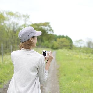 ミラーレス一眼カメラを持つ女性の後姿の写真素材 [FYI04553327]