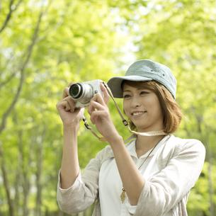 ミラーレス一眼カメラで写真を撮る女性の写真素材 [FYI04553330]