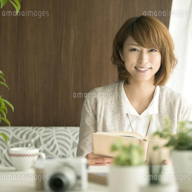 本を持ち微笑む女性の写真素材 [FYI04553334]