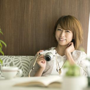 ミラーレス一眼カメラを持ち微笑む女性の写真素材 [FYI04553336]