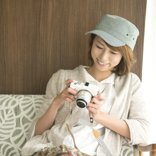 ミラーレス一眼カメラを見る女性の写真素材 [FYI04553337]