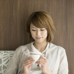 コーヒーカップを持ち微笑む女性の写真素材 [FYI04553338]