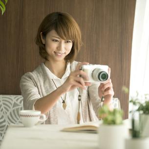 ミラーレス一眼カメラで写真を撮る女性の写真素材 [FYI04553344]