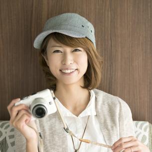 ミラーレス一眼カメラを持ち微笑む女性の写真素材 [FYI04553346]