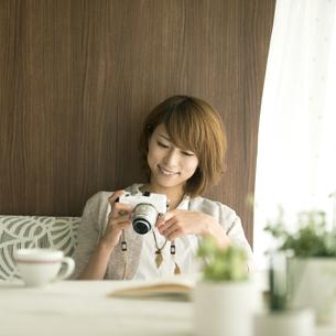 ミラーレス一眼カメラを見る女性の写真素材 [FYI04553347]