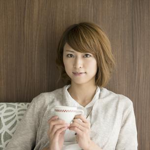 コーヒーカップを持ち微笑む女性の写真素材 [FYI04553348]