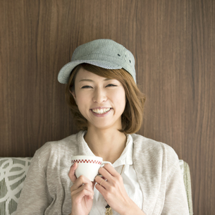 コーヒーカップを持ち微笑む女性の写真素材 [FYI04553350]