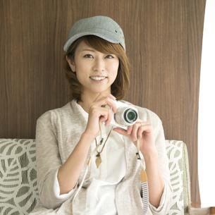 ミラーレス一眼カメラを持ち微笑む女性の写真素材 [FYI04553351]