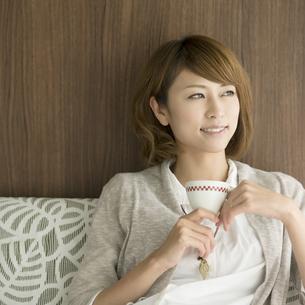 コーヒーカップを持ち微笑む女性の写真素材 [FYI04553353]