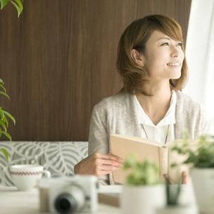 本を持ち窓の外を眺める女性の写真素材 [FYI04553354]