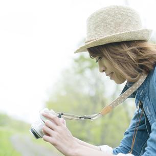 ミラーレス一眼カメラで写真を撮る女性の写真素材 [FYI04553355]