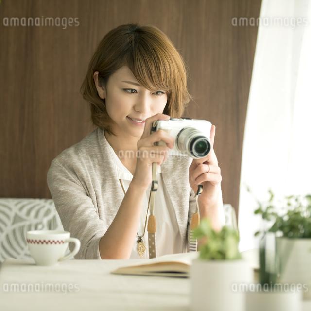 ミラーレス一眼カメラで写真を撮る女性の写真素材 [FYI04553359]