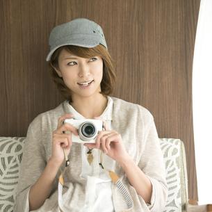 ミラーレス一眼カメラを持ち窓の外を眺める女性の写真素材 [FYI04553361]