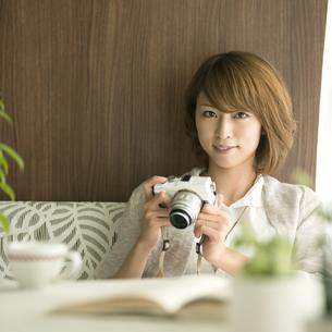 ミラーレス一眼カメラを持ち微笑む女性の写真素材 [FYI04553365]