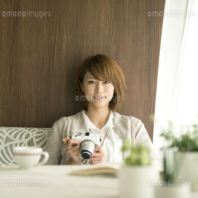ミラーレス一眼カメラを持ち微笑む女性の写真素材 [FYI04553366]