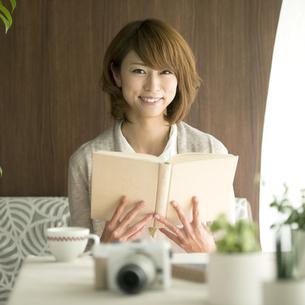本を持ち微笑む女性の写真素材 [FYI04553367]
