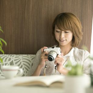 ミラーレス一眼カメラを見る女性の写真素材 [FYI04553369]