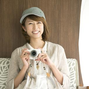 ミラーレス一眼カメラを持ち微笑む女性の写真素材 [FYI04553370]