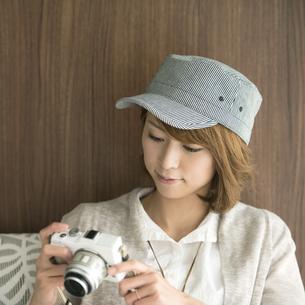 ミラーレス一眼カメラを見る女性の写真素材 [FYI04553371]