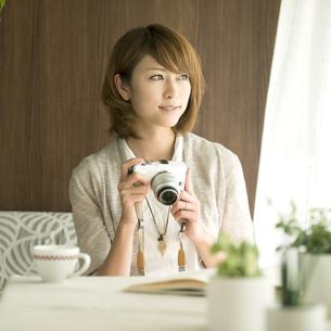 ミラーレス一眼カメラを持ち窓の外を眺める女性の写真素材 [FYI04553372]
