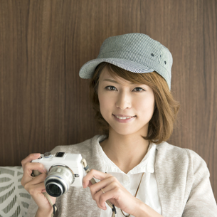 ミラーレス一眼カメラを持ち微笑む女性の写真素材 [FYI04553373]
