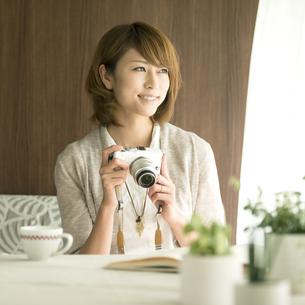 ミラーレス一眼カメラを持ち窓の外を眺める女性の写真素材 [FYI04553377]