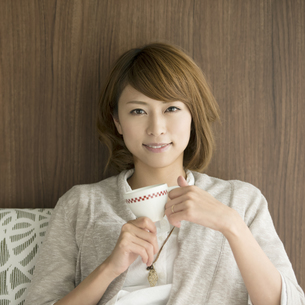コーヒーカップを持ち微笑む女性の写真素材 [FYI04553379]