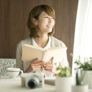 本を持ち窓の外を眺める女性の写真素材 [FYI04553381]