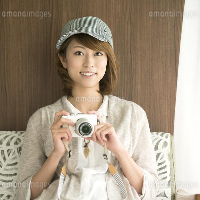 ミラーレス一眼カメラを持ち微笑む女性の写真素材 [FYI04553382]
