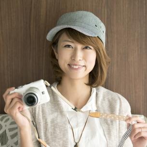 ミラーレス一眼カメラを持ち微笑む女性の写真素材 [FYI04553384]