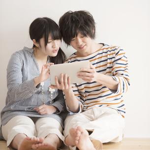 タブレットPCを操作するカップルの写真素材 [FYI04553403]