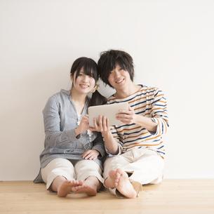 タブレットPCを持ち微笑むカップルの写真素材 [FYI04553404]