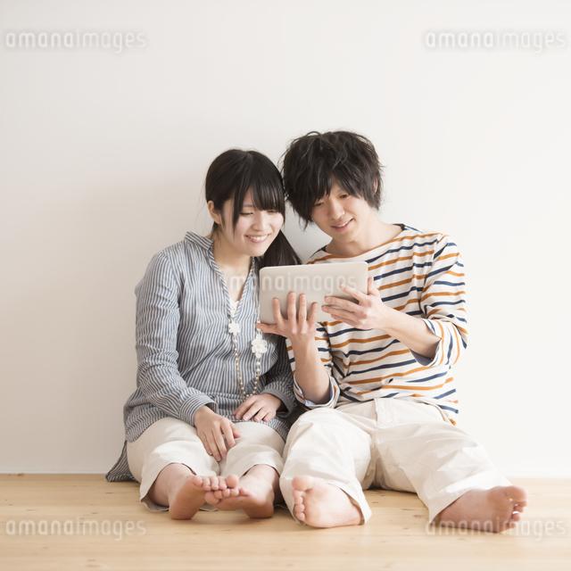 タブレットPCを操作するカップルの写真素材 [FYI04553407]