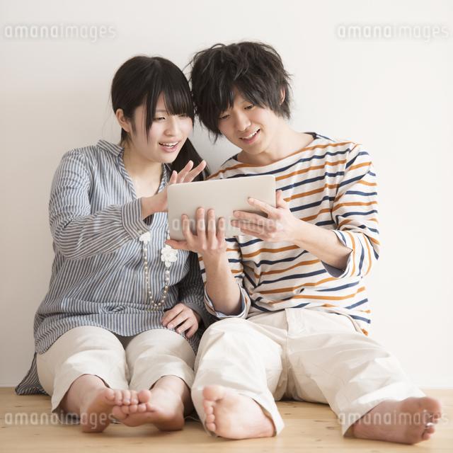 タブレットPCを操作するカップルの写真素材 [FYI04553409]