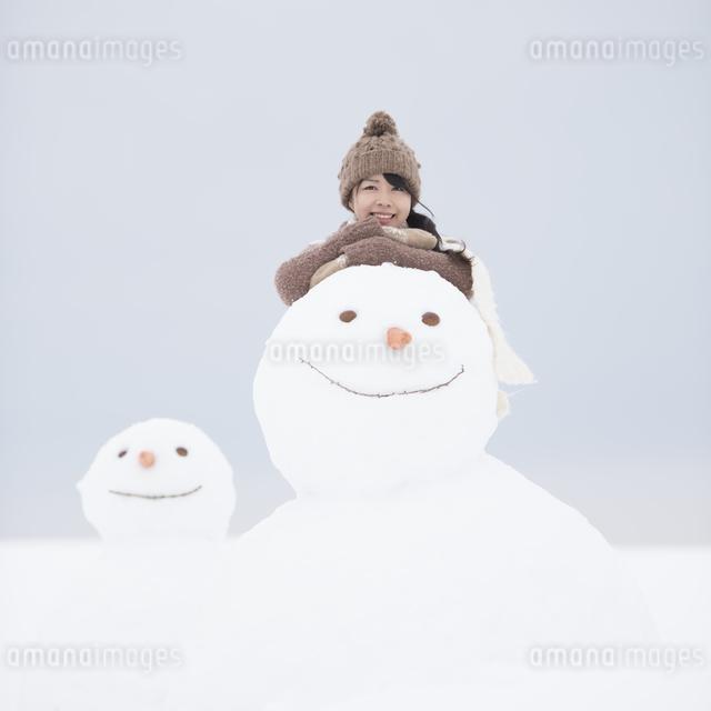 微笑む女性と雪だるまの写真素材 [FYI04553486]
