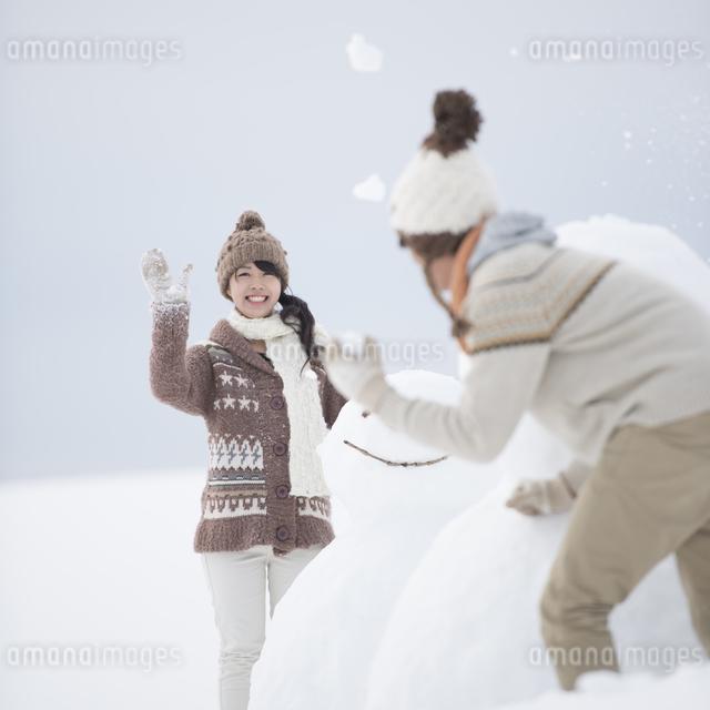 雪だるまの周りで雪合戦をするカップルの写真素材 [FYI04553506]