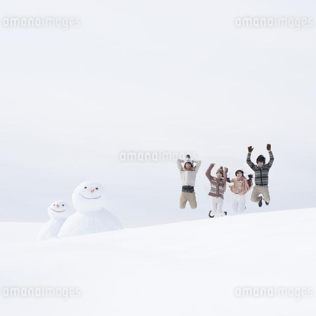 雪原でジャンプをする大学生の写真素材 [FYI04553521]