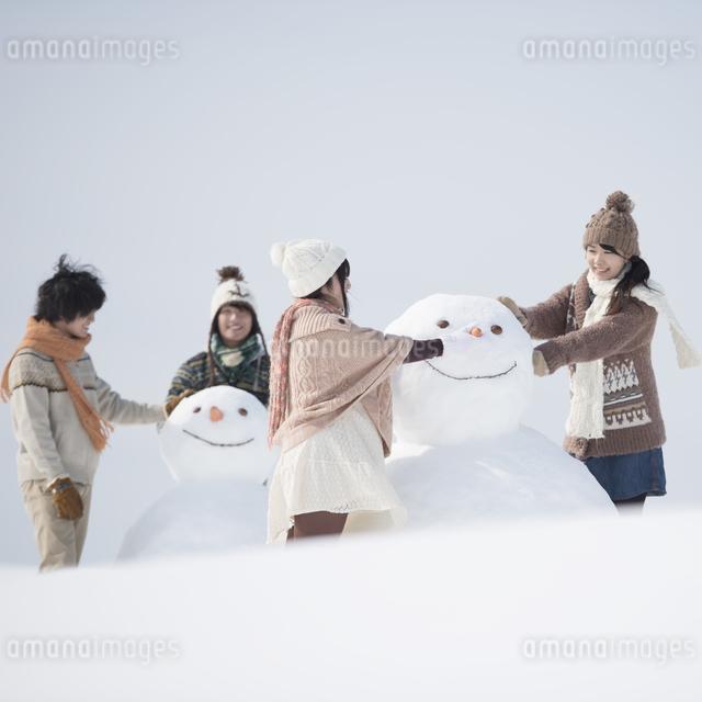 雪だるまを作る大学生の写真素材 [FYI04553544]
