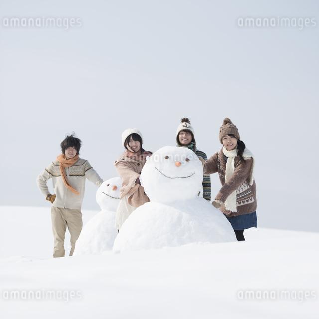 雪だるまの周りで微笑む大学生の写真素材 [FYI04553549]