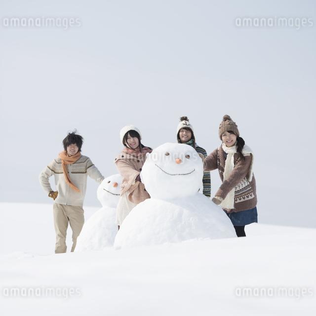 雪だるまの周りで微笑む大学生の写真素材 [FYI04553550]