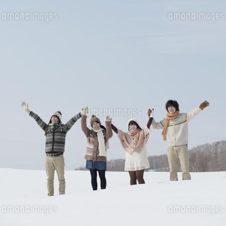 雪原で手をつなぐ大学生の写真素材 [FYI04553565]