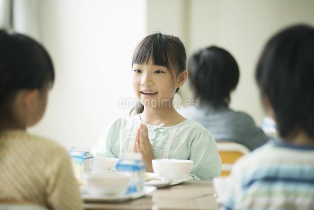 給食を前に手を合わせる小学生の写真素材 [FYI04553585]