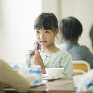 給食を前に手を合わせる小学生の写真素材 [FYI04553587]