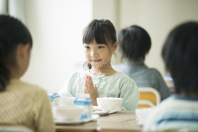 給食を前に手を合わせる小学生の写真素材 [FYI04553588]