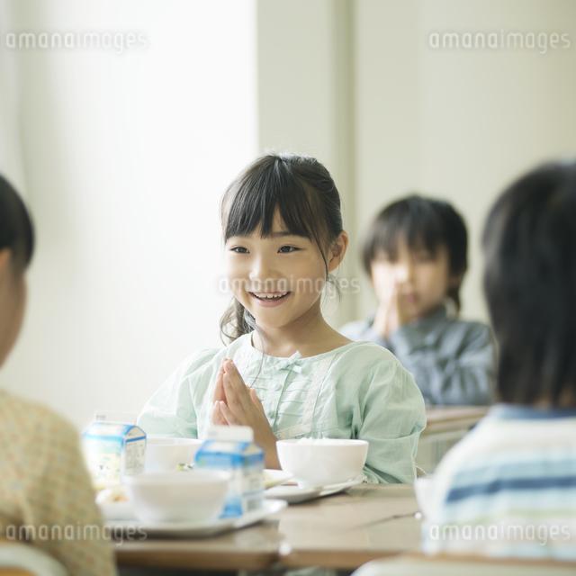 給食を前に手を合わせる小学生の写真素材 [FYI04553589]