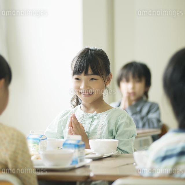 給食を前に手を合わせる小学生の写真素材 [FYI04553590]