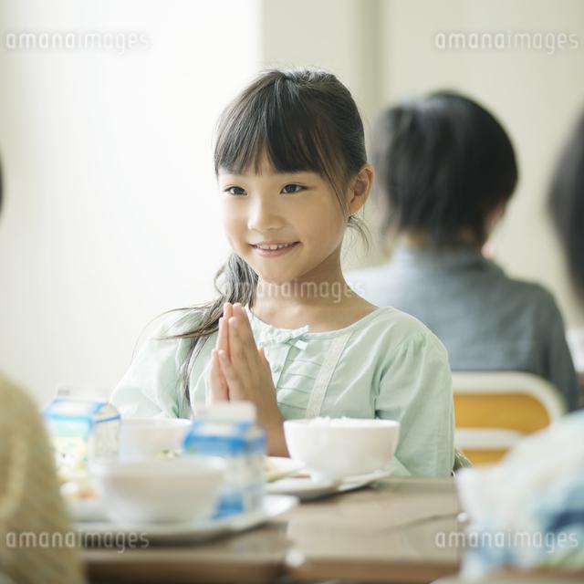 給食を前に手を合わせる小学生の写真素材 [FYI04553591]